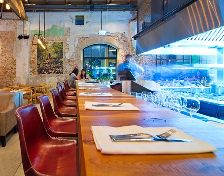 TEL AVIV, AUGUST 15, 2014: Patrons enjoying dinner in a modern open kitchen restaurant in Tel Aviv.  The restaurant is part of the hip Sarona district featuring restored Templer buildings.
