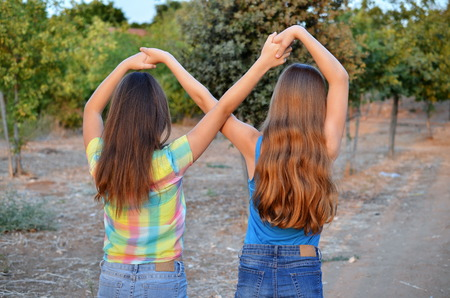 Best Friends Forever - two 12 year old teenage girls  holding hands in an infinity forever sign to signify BFF Stock Photo