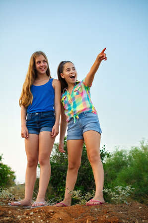 Best Friends Forever - two 12 year old teenage girls pointing in awe and surprise photo