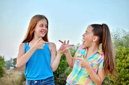 12 year old: Best Friends Forever - two 12 year old teenage girls looking at each other with a surprised emotion Stock Photo