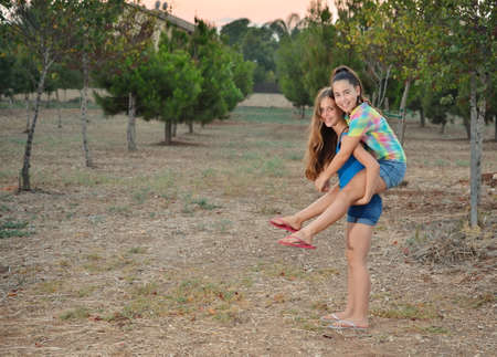 Best Friends Forever - two 12 year old teenage girls  piggy-backing at sunset photo