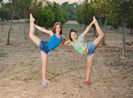 Two 12 year old teenage girls dancers doing the splits photo