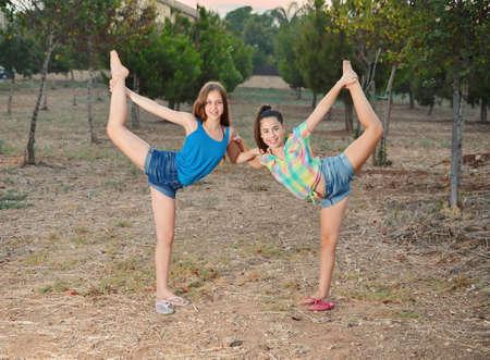 Two 12 year old teenage girls dancers doing the splits