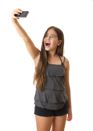 12 year old teenage girl taking a selfie - self portrait with her smartphone with a surprised look on her face - isolated on white photo