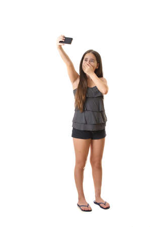 Full body portrait of 12 year old teenage girl taking a selfie - self portrait with her smartphone, covering her mouth - isolated on white photo