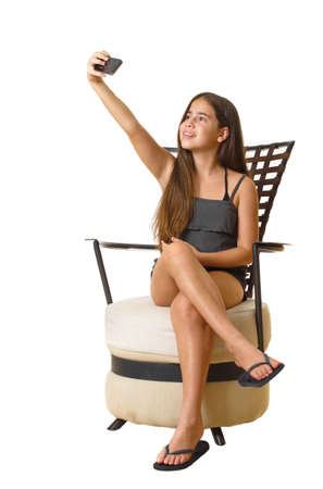 12 year old teenage girl taking a selfie - self portrait with her smartphone - isolated on white - sitting down
