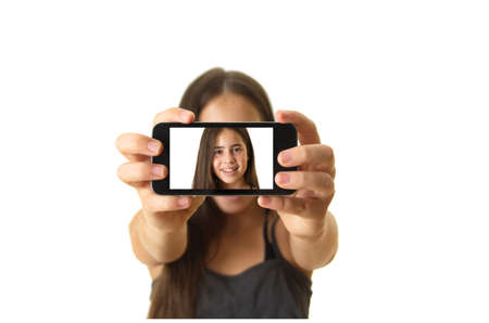12 year old teenage girl taking a selfie - self portrait with her smartphone - isolated on white photo