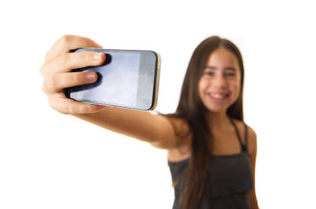 12 year old: 12 year old teenage girl taking a selfie portrait with her smartphone - focus on the phone and the hand - isolated on white Stock Photo