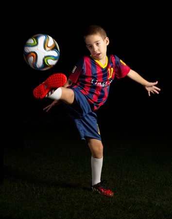 TEL AVIV - AUG 25, 2014: Artistic low key portrait of a boy kicking a world cup football  soccer ball in FC Barcelona blue and red striped Uniform featuring #10 - Lionel Messi