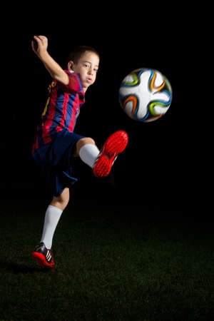 lionel: TEL AVIV - AUG 25, 2014: Artistic low key portrait of a boy kicking a world cup football  soccer ball in FC Barcelona blue and red striped Uniform featuring #10 - Lionel Messi