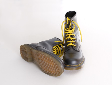 combat boots: A pair of 8 eyelet 8 inch classic unisex black lace-up fashion combat boots with yellow laces and the sole visible