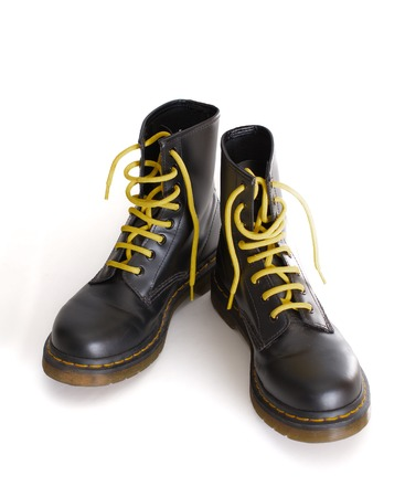 combat boots: A pair of 8 eyelet 8 inch classic unisex black lace-up fashion combat boots with yellow laces