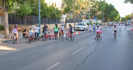 yom kippur: TEL AVIV - OCT. 4, 2014: People walking and riding in the streets on Yom Kippur (Day of Atonement) in Tel Aviv.  There is little car travel and Israelis freely walk, bike and skate on the streets. Editorial
