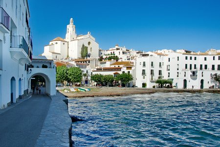 CADQAUES, SPAIN - OCT 8, 2014: Famous white houses and beach of the Costa Brava Cadaques village, former residence of Salvador Dali, in Cap de Creus peninsula, Catalonia, Spain.