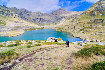 primer: People hiking to Estany Primer - one of the three lakes of Tristaina (Estanys de Tristaina) in Andorra near the Ordino-Arcalis ski resort in the spring