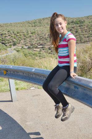 guard rail: Teenage girl relaxing sitting on the guard rail on the Costa Brava, Spain road Stock Photo