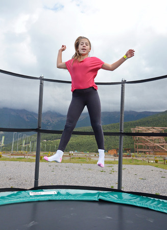 12 year old: 12  year old teenage girl jumping on a trampoline in the Andorra Pyrenees Mountains Stock Photo