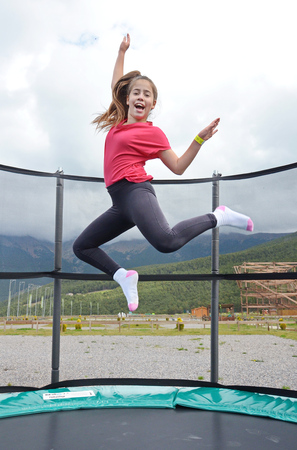 12  year old teenage girl jumping on a trampoline in the Andorra Pyrenees Mountains Standard-Bild