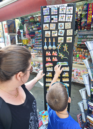 BARCELONA, OCT 13, 2014: Mother and son looking at Barcelona memorabilia and souvenirs on La Rambla boulevard, Spain