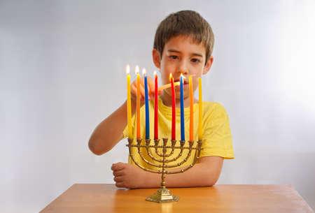hanuka: An Israeli 8 year old child lighting a Hanukkah Menorah