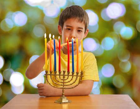 8 year old: An Israeli 8 year old child lighting a Hanukkah Menorah