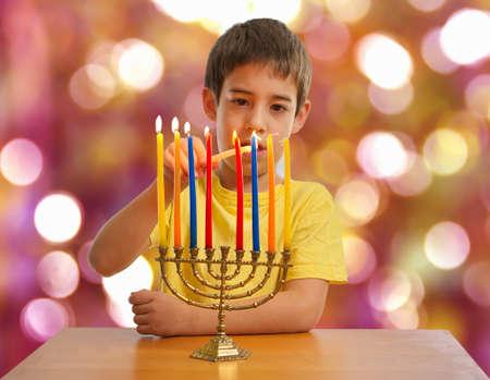 An Israeli 8 year old child lighting a Hanukkah Menorah photo
