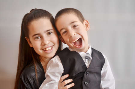 12-year-old Israeli teenager celebrating her Bat Mitzvah with her younger brother - isolated photo