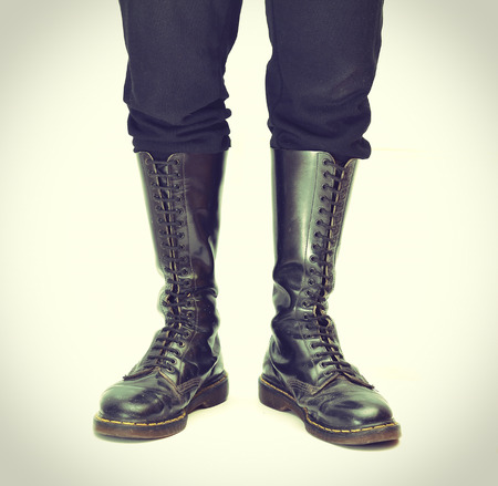 combat boots: A pair of old and rugged mensunisex knee-high black 20-eyelet lace-up combat boots Stock Photo