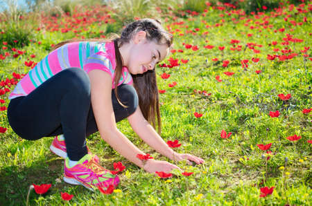windflower: Teenage girl with braces on her teeth in a field of wild red anemone coronaria (windflower)  flowers blooming in the Galilee, Israel, after the winter rains Stock Photo