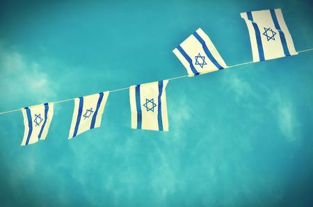 independencia: Banderas de Israel en una cadena en blanco y azul que muestra la estrella de David que cuelga con orgullo para el D�a de la Independencia de Israel (Iom Haatzmaut) - efecto retro vendimia