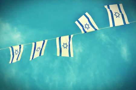 celebration day: Israel flags in a chain in white and blue showing the Star of David hanging proudly for Israels Independence Day (Yom Haatzmaut) - vintage retro effect