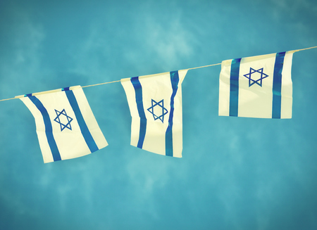 Israel flags in a chain in white and blue showing the Star of David hanging proudly for Israels Independence Day (Yom Haatzmaut) - vintage retro effect
