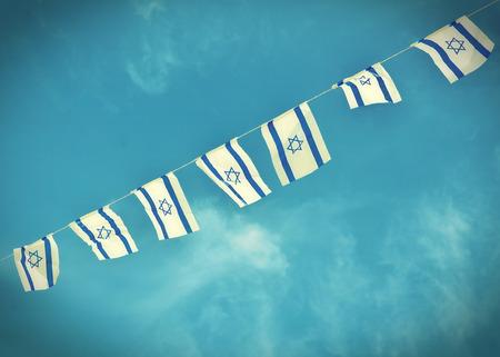 白と青を示すイスラエル共和国の独立記念日 (ヨム ・ Haatzmaut) - ビンテージ レトロな効果を誇らしげにぶら下がっている星の David のチェインにイス