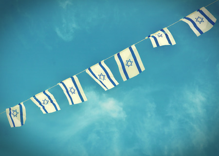 Israel flags in a chain in white and blue showing the Star of David hanging proudly for Israel's Independence Day (Yom Haatzmaut) - vintage retro effect Фото со стока