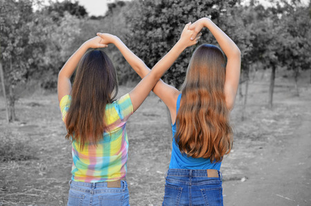 Best Friends Forever - two 12 year old teenage girls  holding hands in an infinity forever sign to signify BFF - color over black and white for strong subject focus