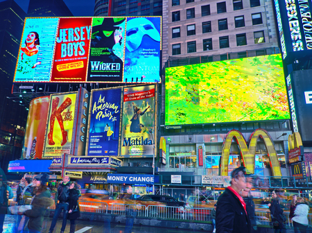 miserable: NEW YORK, MARCH 14, 2015: Times Square at night - HDR featuring the flagship McDonalds restaurant and lighted signs for Kinky Boots, Matilda, Le Miserable, and other famous shows.