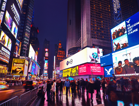 NEW YORK, MARCH 14, 2015: Times Square at night - HDR featuring busy Broadway with animated signs for the Lion King and other shows.  Theater District is a symbol of New York and the United States.