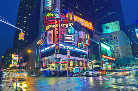 NEW YORK, MARCH 14, 2015: Times Square at night - HDR featuring the flagship Hershey's chocolate store and many Broadway style animated signs.