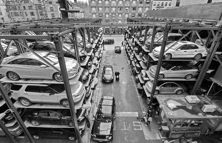 a lot  of: NEW YORK - MARCH 11, 2015: People and cars in a busy multi-level parking garage in mid-town Manhattan, New York City, USA - black and white