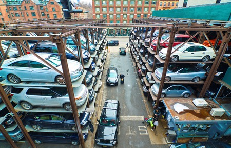 NEW YORK - MARCH 11, 2015: People and cars in a busy multi-level parking garage in mid-town Manhattan, New York City, USA