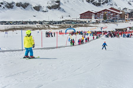 kids at the ski lift: ZURS, AUSTRIA - APRIL 10, 2015: Kids skiing in a the Zurs - Lech, Arlberg, ski school. Parents and spectators are watching the kids racing on the final school day.  Conveyor is used to go up the hill.