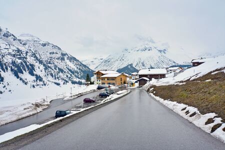chalets: Look above the Lech ski resort, part of the Arlberg Lech-Zurs ski area, from the road climbing to Oberlech.  Showing snow covered chalets, mountains, and ski pistes. Stock Photo