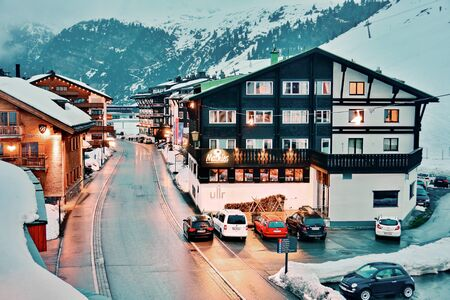 chalets: ZURS, AUSTRIA - APRIL 11, 2015: Evening in the hamlet of Zurs, part of the Arlberg Lech-Zurs ski resort.  Showing snow covered chalets, mountains, and ski pistes.