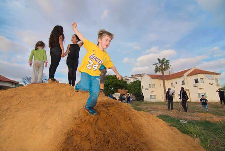 bonfires: TEL AVIV, ISRAEL - MAY 3, 2015: Elementary school kids playing on a dirt hill near festive Lag Baomer bonfires in a secular suburb of Tel Aviv, Israel