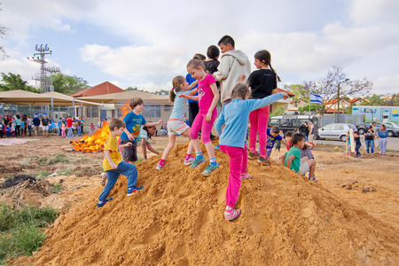 secular: TEL AVIV, ISRAEL - MAY 3, 2015: Elementary school kids playing on a dirt hill near festive Lag Baomer bonfires in a secular suburb of Tel Aviv, Israel