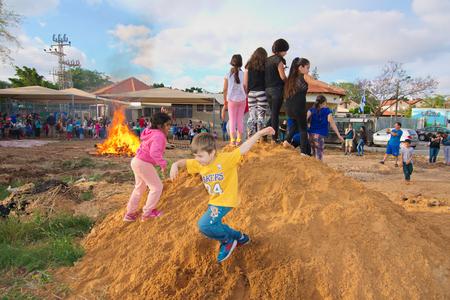 lag: TEL AVIV, ISRAEL - MAY 3, 2015: Elementary school kids playing on a dirt hill near festive Lag Baomer bonfires in a secular suburb of Tel Aviv, Israel