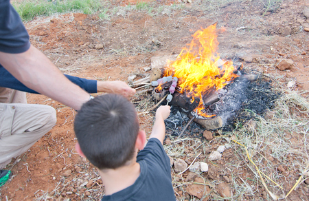 lag: Elementary school kids roasting marshmallow on a bonfire during festive Lag Baomer celebrations Stock Photo