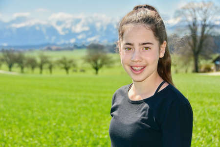 14 year old Israeli teenager girl in the Switzerland country with green fields and snow-capped mountains in the background