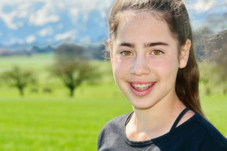12 13: 14 year old Israeli teenager girl in the Switzerland country with green fields and snow-capped mountains in the background