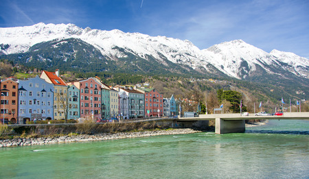 innsbruck: INNSBRUCK, AUSTRIA - APRIL 9, 2015: Historic architecture, snow capped mountains, and the Inn river in the old alpine town of Innsbruck, Tyrol, Austria.
